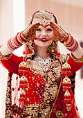 'A Bride With Blond Hair Wearing A Red And Gold Sari And Jewelry Holding Her Mehndi Covered Hands In A Heart Shape; Ludhiana, Punjab, India'