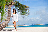 'A Woman In A White Dress Posing Beside A Palm Tree On A Beach; Punta Cana, La Altagracia, Dominican Republic'