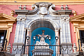 'Building with ornate facade and a sculpture with lights on a railing;Malaga andalusia spain'