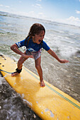 'A young girl on a yellow surfboard;Gold coast queensland australia'