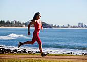 'A woman runs on a path along the water;Gold coast queensland australia'