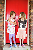 'Two girls standing in front of a red door making silly expressions at one another;Gold coast queensland australia'