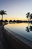 'Sunset and palm trees reflecting in a pool at the bora bora nui resort and spa;Bora bora island society islands french polynesia south pacific'