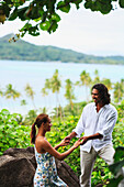 'A Man And Woman Hold Hands With A View Of The Ocean At Bora Bora Nui Resort And Spa; Bora Bora Island Society Islands French Polynesia South Pacific'