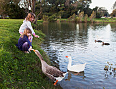 'Two Young Girls Feed Birds At The Water's Edge; Currumbin Valley Gold Coast Queensland Australia'