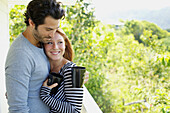 'A couple on a balcony with their coffee mugs;Wailua kauai hawaii united states of america'
