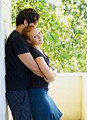 'A man and woman standing in an embrace on a balcony;Wailua kauai hawaii united states of america'