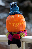 Close Up Of A Carved Pumpkin With The Word Alaska Carved As Teeth And Sitting On Deck Railing And Wearing A Knit Stocking Cap And Scarf, Kodiak, Southwest Alaska, Autumn