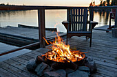 'Fire pit on a wooden dock on a lake at sunset;Lake of the woods ontario canada'
