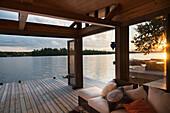 'Covered patio on a wooden deck on the water's edge at sunset;Lake of the woods ontario canada'