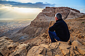 'A man sits on a rock looking out over the judean desert;Israel'