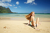 'A young woman sitting in the sand along the ocean at the coast;Kauai hawaii united states of america'