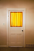 'Interior door of a 1920's farmhouse with yellow curtains on the window;Parkland county alberta canada'