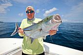 'Man holds fresh caught jack fish; panama'