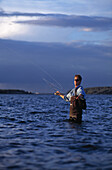 'A man fishing while standing in the water; boston massachusetts united states of america'