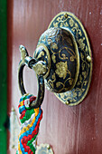 'Ornate doorknob with colourful fabric hanging from the ring;Lhasa xizang china'