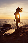 'Silhouette of a woman standing on a rock at the water's edge with her surfboard at sunset;Tarifa cadiz andalusia spain'
