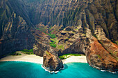 'Blue water and white sand in a small inlet along a rugged coastline;Hawaii united states of america'