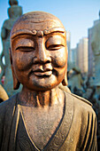 'Bronze faced buddha statue glowing in warm light;Beijing china'