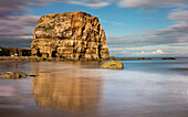 'Large rock formation on the coast reflected in the wet sand;South shields tyne and wear england'