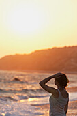 'A young woman stands at the water's edge watching the sunset;Aphrodite bay, cyprus'