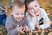 'Portrait of two young boys laying on fallen leaves in autumn colours;St. albert alberta canada'