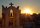 'Cross and bell on a structure at sunset;Oia greece'