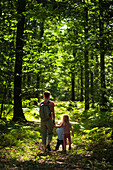 'Mother with boy and girl walking along trail in oak forest;Brittany france'