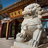 Close up of a lion statue outside a building in traditional japanese architecture