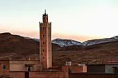 A tower in the midst of buildings with mountains in the background at sunset