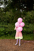 'A girl holding pink balloons in front of her face;Pacifica california united states of america'