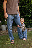 'A young boys holds onto his father's leg;Pacifica california united states of america'