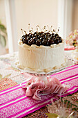 'A white iced cake topped with fresh cherries on a pink table runner;California united states of america'
