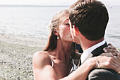 'A bride and groom kissing on a beach at the water's edge;Kirkland washington united states of america'