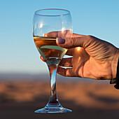'A woman's hand holding a glass of white wine;Souss-massa-draa morocco'