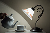 'A Lamp Shining On A Hand Holding A Teapot Pouring Tea Into A Teacup; Sestri Levante, Emilia-Romagna, Italy'