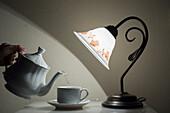 'A Lamp Shining On A Hand Holding A Teapot Pouring Tea Into A Teacup; Sestri Levante, Emilia-Romagna, Italy'