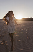 'A Young Woman With Long Hair Running On The Beach At Sunset; Tarifa, Cadiz, Andalusia, Spain'