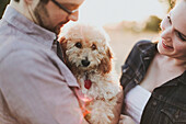 'A Couple Holding Their Pet Dog; Crescent Beach, British Columbia, Canada'