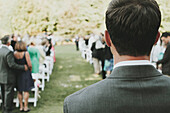 'A Man Standing At The Top Of The Aisle At An Outdoor Wedding; Kirkland, Washington, United States Of America'
