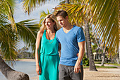 'A couple walk on a beach with palm trees along the water's edge; Honolulu, Hawaii, United States of America'