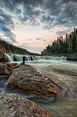 'A person watches as the Trout River flows over Sambaa Deh Falls in Sambaa Deh Territorial Park; Northwest Territories, Canada'