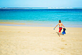 'A boy running out to the ocean across the beach with snorkelling gear; Kauai, Hawaii, United States of America'