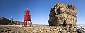 'Groyne lighthouse beside a rock formation along the shoreline; South Shields, Tyne and Wear, England'