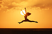 'Silhouette of a woman leaping in the air with the golden sky and sun in the background; Tarifa, Costa de la Luz, Cadiz, Andalusia, Spain'