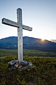A cross (Christian symbol) sits on knoll in valley in Alaska Range, Southcentral Alaska, Summer