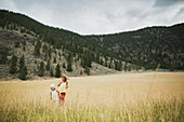 'Two young girls walking in the tall grass of a field; Peachland, British Columbia, Canada'