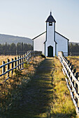 'Old wooden church in foothills with wooden fence and blue sky; Cochrane, Alberta, Canada'