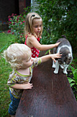'Brother and sister pet their cat outside in the garden; Toronto, Ontario, Canada'