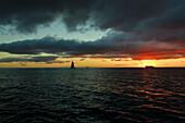'A sailboat on the ocean water off the coast of Waikiki at sunset; Waikiki, Oahu, Hawaii, United States of America'